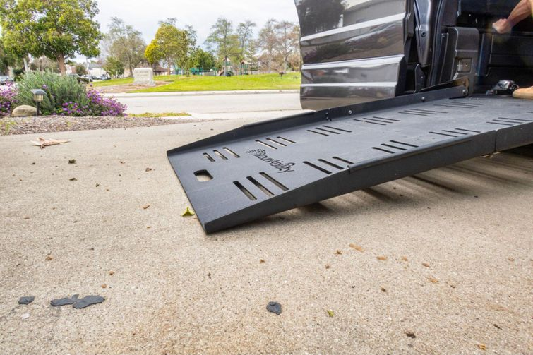 Wheelchair accessible vehicle puts ramp down for customer in a wheelchair.