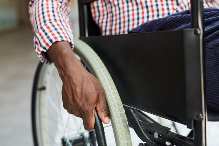 Disabled person in a wheelchair waiting for paratransit service.